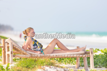 woman sunbathing on tropical beach