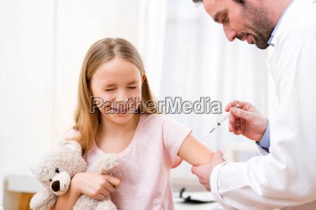 junges kleines maedchen beim arzt geimpft