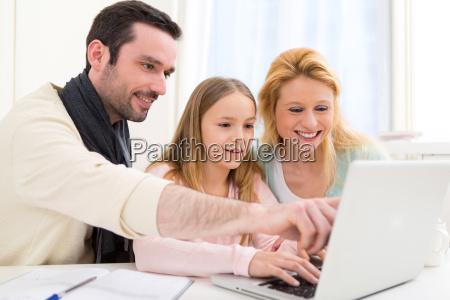 glueckliche familiedie vor einem laptop