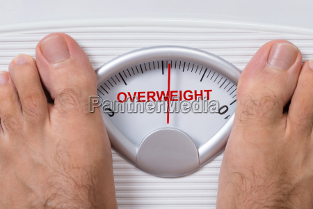 feet on weight scale indicating overweight