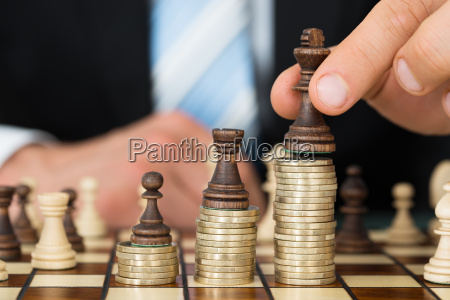 businessman placing chess pieces on stacked