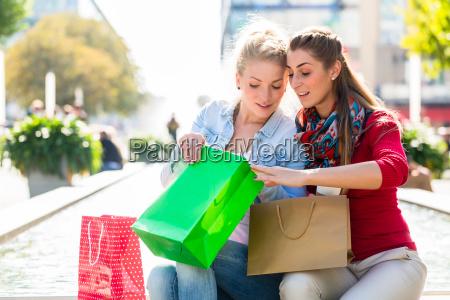 frauen beim einkaufen mit einkaufstueten in