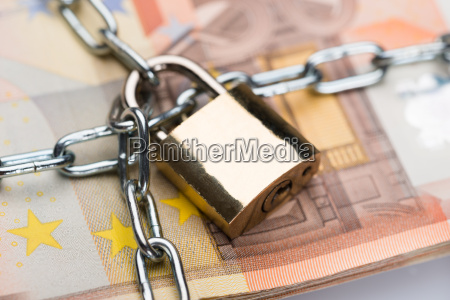 chain and padlock around euro banknotes