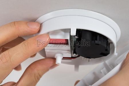 handyman repairing smoke detector