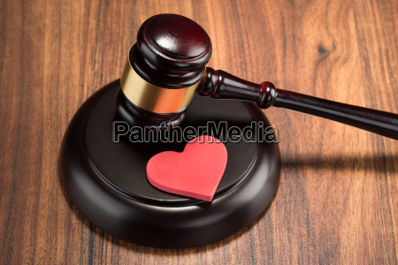 gavel and red heart on table