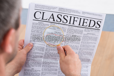 man looking classifieds through magnifying glass