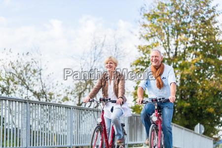senioren paar mit fahrraedern auf bruecke