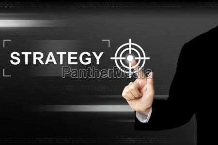 business hand drueckt strategie taste auf