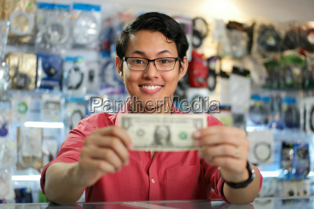 happy chinese man showing first dollar