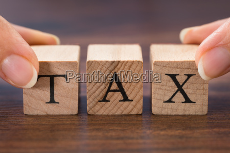 person hand holding the word tax