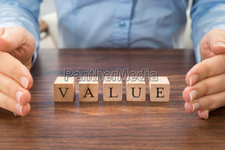businessperson with value word on blocks