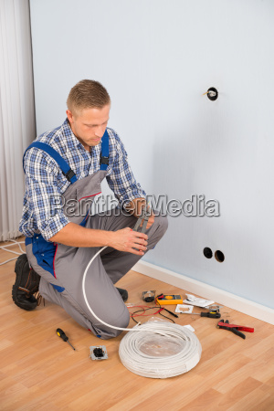 electrician working with wire with plier