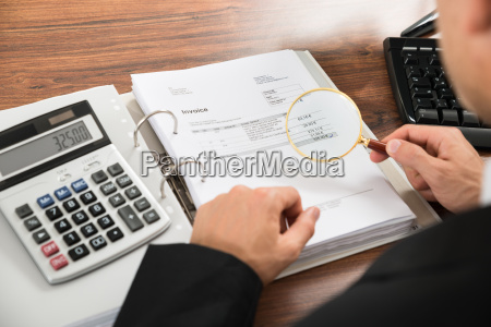 businessman looking at invoice through magnifying