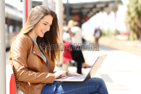 girl using a laptop while waiting