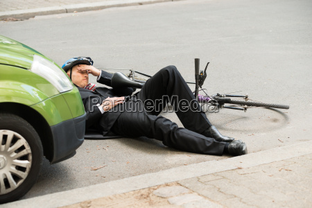 male cyclist after car accident on