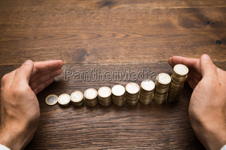 businessmans hand protecting coins on desk