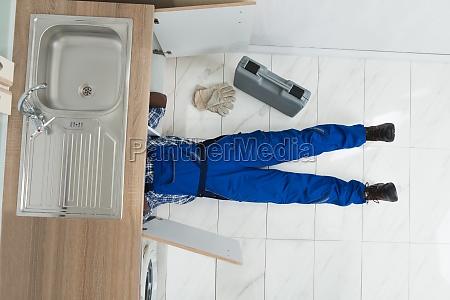 handyman repair sink in kitchen