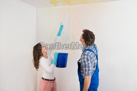 woman showing water leaking from ceiling