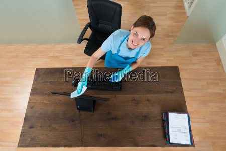 woman cleaning keyboard at desk