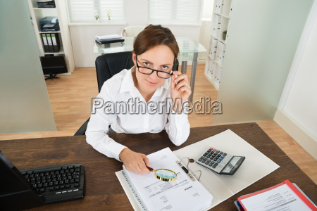 businesswoman with invoice and magnifying glass
