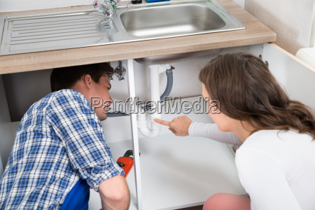 woman showing damage in sink pipe
