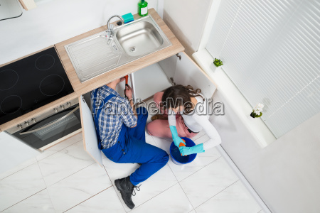 repairman fixing pipe while woman squeezing