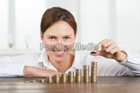 businesswoman placing coin to stack of