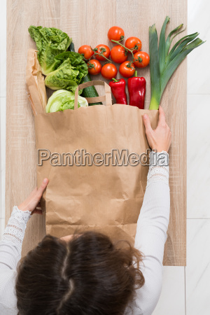 woman removing vegetables from shopping bag