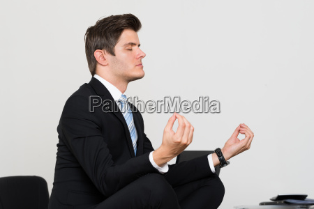 businessman doing meditation in office