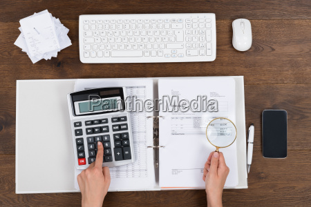 person checking invoice with magnifying glass