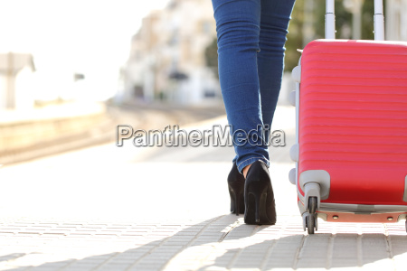 traveler legs walking with luggage in