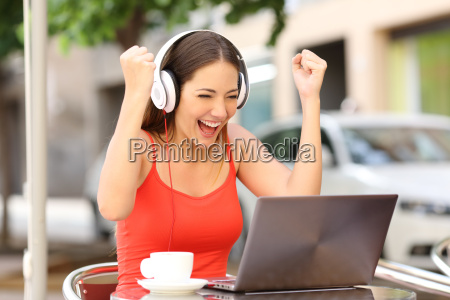 winner girl euphoric watching a laptop