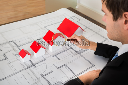 architect looking at house models through