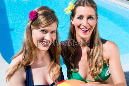 freundinnen baden am swimming pool im