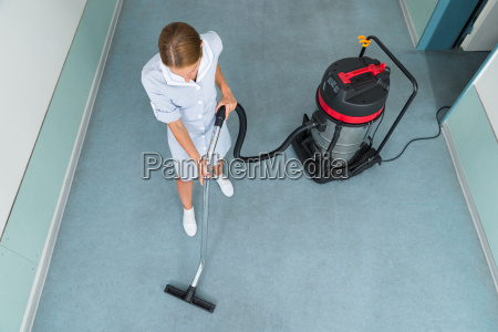 female worker cleaning with vacuum cleaner