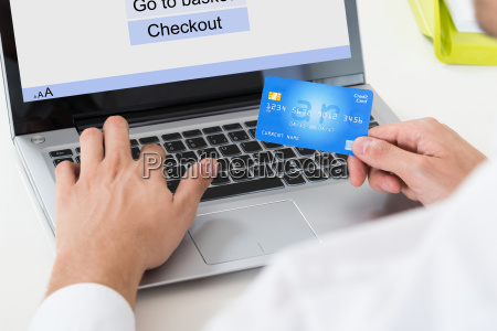businessperson using laptop and credit card