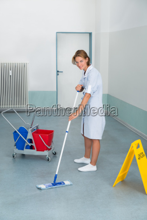 janitor with wet caution sign and