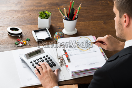 businessman inspecting invoice at desk