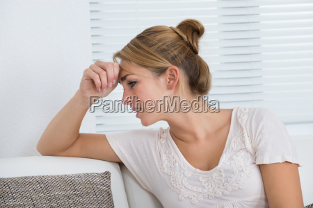 woman suffering from headache while sitting