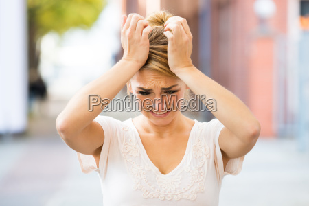 woman suffering from headache outdoors