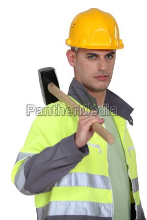 labourer carrying a mallet