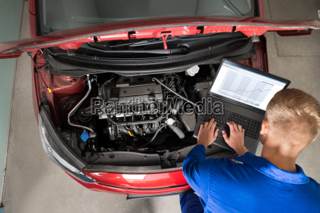 mechanic examining car engine with help