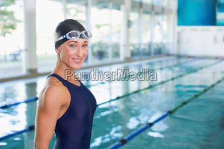 fit female swimmer by pool at