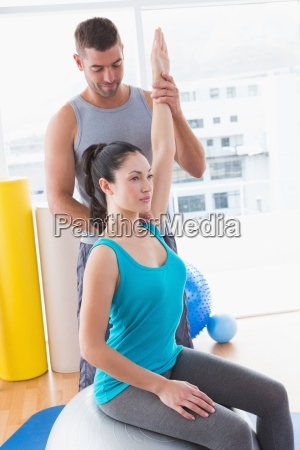 trainer assisting woman exercising on fitness