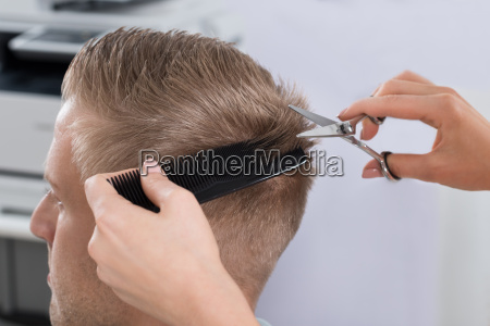 man getting haircut from hairdresser at
