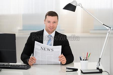 businessman holding newspaper at desk in