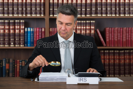 auditor examining documents with magnifying glass