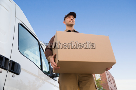 delivery man carrying cardboard box by