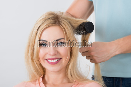 hairstylist brushing womans hair at salon