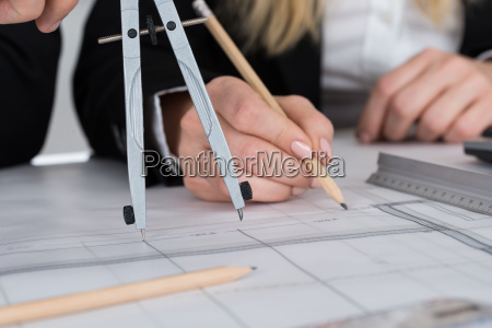 architects working on blueprint at desk
